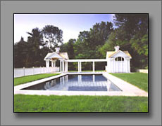 View of pool with classical pool house.